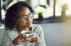 Mulher africana nova que senta-se em um café que aprecia algum café fotos de stock