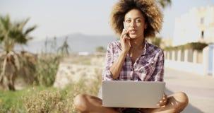 Mulher africana nova que trabalha no portátil na natureza
