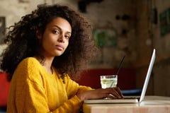 Mulher africana nova séria que trabalha no portátil em um café fotografia de stock royalty free