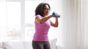 Mulher africana que exercita com pesos em casa video estoque