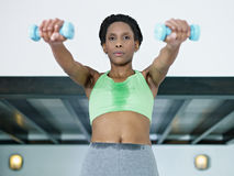 Mulher africana que exercita com pesos pequenos na ginástica Imagens de Stock Royalty Free