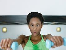 Mulher africana que exercita com pesos pequenos na ginástica Fotografia de Stock Royalty Free