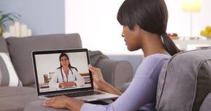 Mulher africana que fala com o doutor em linha foto de stock royalty free