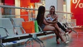 Mulher africana que fala e que verifica o smartphone após a compra no shopping filme