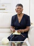 Mulher africana que faz malha no sofá em casa Fotografia de Stock Royalty Free