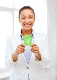 Mulher africana que guardara a casa do papel verde fotografia de stock royalty free