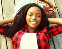 Mulher africana relaxado em um assoalho de madeira com mãos atrás da cabeça fotografia de stock royalty free