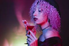 Mulher afro étnica que bebe um cocktail vermelho do Dia das Bruxas com um cherr Fotografia de Stock Royalty Free
