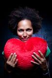 Mulher afro-americana com um coxim Heart-Shaped fotografia de stock royalty free