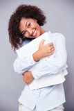 Mulher afro-americana de sorriso que está com dobradores Fotografia de Stock