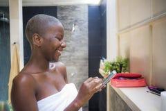 mulher afro-americana do viciado feliz e atrativo do Internet no banheiro home envolvido na toalha usando o telefone celular fotografia de stock