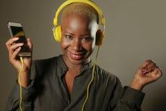 Mulher afro-americana feliz e atrativa nova com fones de ouvido e telefone celular amarelos que escuta a música ch de sorriso da  imagem de stock