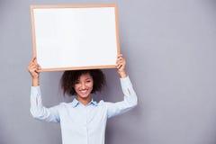 Mulher afro-americana feliz que guarda a placa vazia Imagens de Stock
