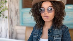 Mulher afro-americana nova nos vidros e no chapéu que morde um bordo, revestimento vestindo das calças de brim foto de stock royalty free