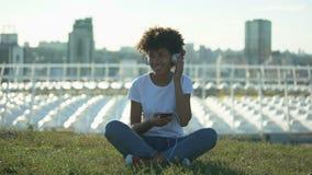 A mulher afro-americana nova que escuta a música nos auriculares, sentando-se no gramado, relaxa filme