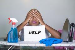 Mulher afro-americana preta atrativa e infeliz nova isolada na placa do ferro da cozinha que guarda o bloco de notas com o feeli  imagens de stock