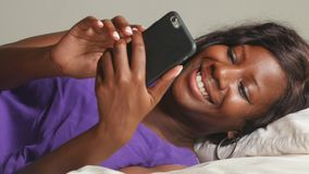 Mulher afro-americana preta bonita e feliz nova que senta-se na cama usando trabalhos em rede relaxados de sorriso do telefone ce filme