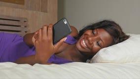 Mulher afro-americana preta bonita e feliz nova que senta-se na cama usando trabalhos em rede relaxados de sorriso do telefone ce vídeos de arquivo
