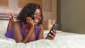 Mulher afro-americana preta bonita e feliz nova que senta-se na cama usando trabalhos em rede relaxados de sorriso do telefone ce video estoque