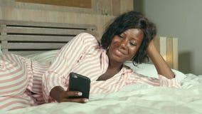 Mulher afro-americana preta bonita no sorriso relaxado de encontro dos pijamas trabalhos em rede de utilização alegres e frescos  video estoque