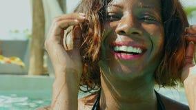 A mulher afro-americana preta feliz e bonita nova no biquini que tem o divertimento na piscina tropical da estância de verão rela filme