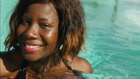 A mulher afro-americana preta feliz e bonita nova no biquini que tem o divertimento na piscina tropical da estância de verão rela video estoque