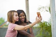Mulher afro-americana preta feliz e bonita nova que aprecia feriados no recurso tropical com a amiga asiática que toma o selfie foto de stock