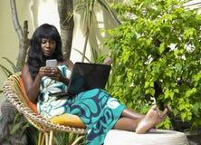Mulher afro-americana preta feliz no vestido elegante que trabalha na casa de campo luxuosa do terraço com portátil e telefone ce imagem de stock