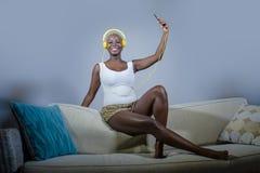 Mulher afro-americana preta relaxado feliz e bonita nova que escuta a música com os fones de ouvido e o telefone celular que apre foto de stock royalty free