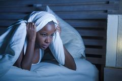 Mulher afro-americana preta triste e forçada nova que encontra-se na virada da cama que tenta dormir anxi de sofrimento da insôni imagem de stock