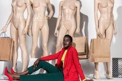 mulher afro-americano à moda que olha a câmera ao sentar-se na frente dos manequins com sacos de papel fotografia de stock