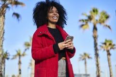 Mulher afro-americano alegre encantador que usa a conexão sem fio livre ao Internet e ao smartphone moderno Fotografia de Stock
