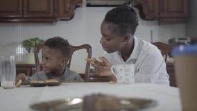 Mulher afro-americano atrativa do retrato que senta-se com seu filho pequeno pela tabela que joga cookies na placa video estoque