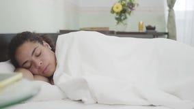 Mulher afro-americano atrativa que dorme sob a cobertura branca na sala clara no fundo Telefone celular que encontra-se sobre filme