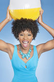 Mulher afro-americano atrativa que guardara a bola de praia no alto sobre o fundo colorido Fotografia de Stock Royalty Free