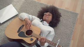 Mulher afro-americano bonita com um penteado afro que encontra-se no assoalho que joga a opini?o superior da guitarra filme