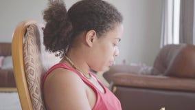 Mulher afro-americano bonita do retrato que senta-se no close-up de observação do jornal da poltrona Menina feliz que relaxa em c filme