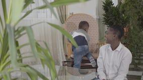 Mulher afro-americano bonita feliz que joga com seu filho engraçado pequeno na sala de visitas acolhedor Mamã do relacionamento e vídeos de arquivo