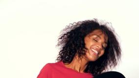 Mulher afro-americano bonita nova na parte superior vermelha que aprecia e que dança com registros de vinil no fundo branco moder vídeos de arquivo