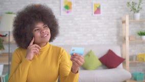 Mulher afro-americano bonita positiva e entusiástica com um penteado afro que olha o cartão de banco no seu video estoque