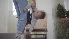 Mulher afro-americano bonita que joga com seu filho bonito e engraçado pequeno e que torce o em seus braços r video estoque