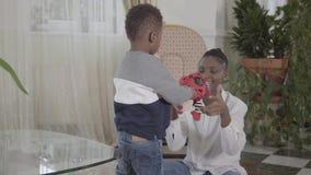 Mulher afro-americano bonita segura que joga com seu filho engraçado pequeno na sala de visitas acolhedor r filme