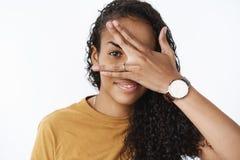 A mulher afro-americano bonito ansiosa vê que amigos preparados cobrindo a cara com a palma e espreitar deleitado completamente foto de stock