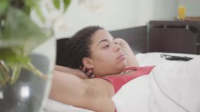 Mulher afro-americano bonito do retrato que encontra-se na cama Menina adorável que relaxa em casa Dia livre da senhora vídeos de arquivo