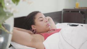 Mulher afro-americano bonito que encontra-se na cama Menina adorável que relaxa em casa Dia livre da senhora vídeos de arquivo
