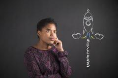 Mulher afro-americano com mão no queixo que pensa sobre o sucesso que sobe rapidamente no fundo do quadro-negro fotografia de stock