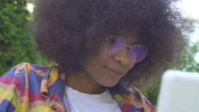 A mulher afro-americano com um penteado afro desabilitou em uma cadeira de rodas usa um sunflare do portátil no fim do parque aci filme