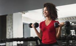 Mulher afro-americano da aptidão que faz exercícios do bíceps no gym fotos de stock