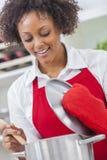 Mulher afro-americano da raça misturada que cozinha a cozinha imagem de stock