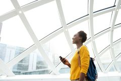 Mulher afro-americano de sorriso com saco e telefone celular na estação imagem de stock